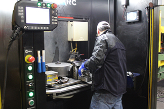Image of welding operator checking fixturing in robotic MIG welding cell
