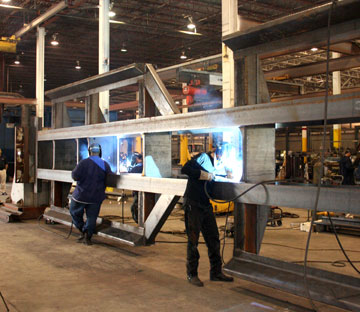 Image of two welders in a trailer manufacturing plant welding on a long run