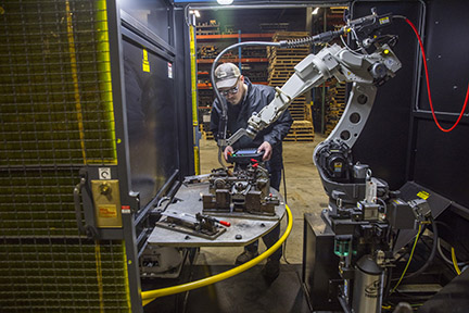 Image of a robotic operator with a teach pendant by a robotic MIG welding cell