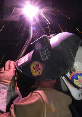 Image of a person welding with a DuraFlux MIG gun while welding over their head