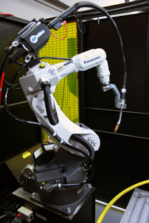 Image of a robotic MIG gun on a robot in a welding cell