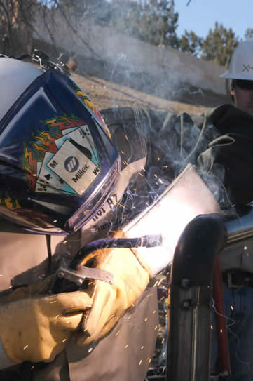 Image of welder using a Dura-FluX MIG gun, welding in the hot Arizona sun at Hot AZ Hell Welding and Fabrication
