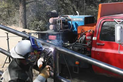 A welder using a Dura-Flux gun to weld a metal guardrail