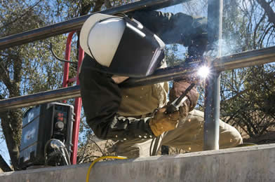 Image of a welder at the HotAz Hell Welding and Fabrication welding while leaning through a railing at a hard to reach weld using the Dura-Flux MIG gun