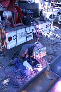 image of a welder in an outdoor, rugged setting