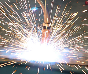 Close up image of a MIG gun with sparks as bright as fireworks
