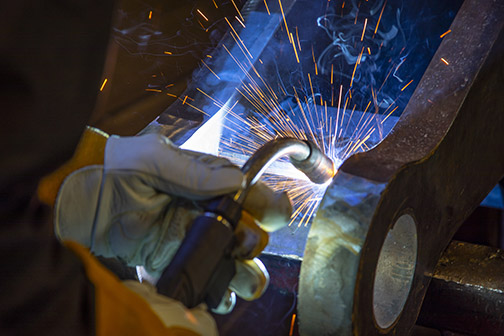 Image of a person welding with a semi-automatic MIG gun