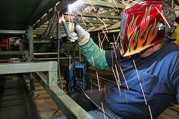 Image of a welder with arm welding above their head