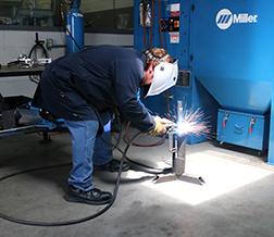 Man bending over welding that shows improper welding ergonomics