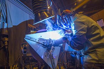 Image of  a welder on using a MIG gun
