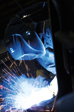 Image of a welder, looking down while welding